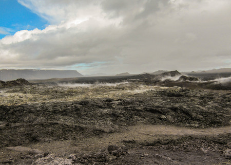 Dramatic landscape with dry stiff black lava, still steaming in Krafla volcanic caldera and fissure zone, Myvatn region. Popular tourist destination of Diamond circle in north of Iceland, Europe