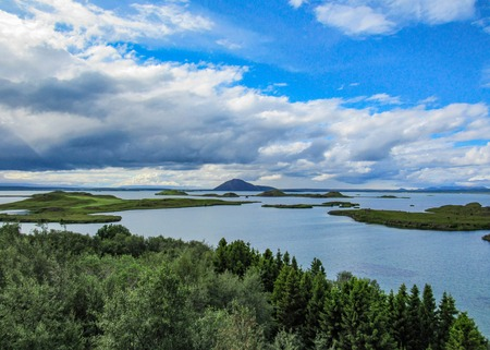 Beautiful landscape of Lake Myvatn with green pseudocraters and islands at Skutustadagigar in beautiful sunny day with blue sky. Popular tourist destination in north of Iceland, Europe Banco de Imagens
