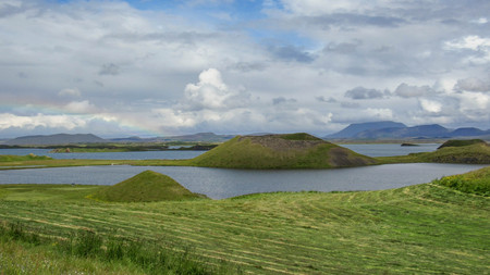 Scenic panorama of Myvatn Lake with green pseudocraters and islands at Skutustadagigar in beautiful sunny day with blue sky and clouds, in gorgeous route of Diamond Circle, North of Iceland, Europe
