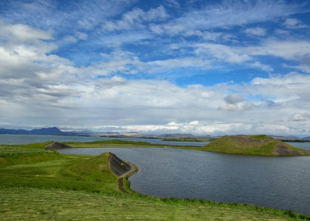 Scenic view of of Myvatn Lake with green pseudocraters and islands at Skutustadagigar in beautiful sunny day with blue sky and clouds. Popular tourist destination in north of Iceland, Europe