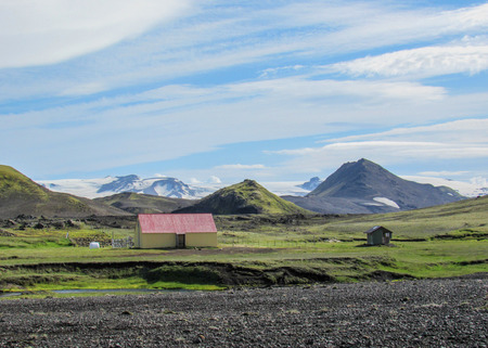 Scene of Hvanngil green valley, small houses, volcanic mountains and Myrdalsjokull ice-cap above Katla volcano with blue sky, Laugavegur Trail between Emstrur-Botnar and Alftavatn, central Iceland