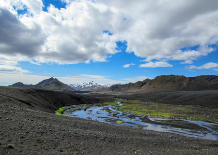 Breathtaking view on tiny river with bright green mossy banks flows from Myrdalsjokull through volcanic barren landscape, hiking on the Laugavegur Trail between Emstrur-Botnar and Alftavatn, Iceland