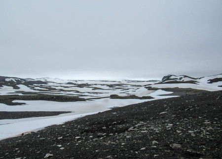 Volcanic white and black landscape of Fimmvorduhals with white snow and black stones. Contrasts of Icelandic nature, Fimmvorduhals Trek from Skogar to Thorsmork, Highlands of Iceland