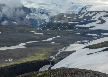 Epic landscape with Myrdalsjokull glacier melting and small waterfall, in the clouds, Fimmvorduhals Trek from Skogar to Thorsmork, Highlands of Iceland