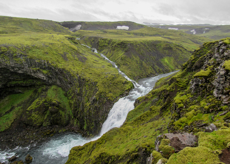 Beautiful mossy landscape along the Skoga river canyon with waterfall in rainy summer day on the Fimmvorduhals Trek from Skogar to Thorsmork, Highlands of Iceland Stock fotó