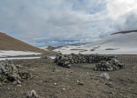 Wind protection walls maden from volcanic rocks for tent in Hrafntinnusker campsite, Laugavegur hike, Fjallabak Nature Reserve, Highlands of Iceland, Europe Stok Fotoğraf - 114653127