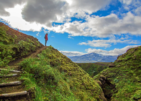 Successful hiker woman standing alone into the wild on the mountain top and looking to new scenic, breathtaking destinations summer vacations outdoor Travel Lifestyle wanderlust adventure concept