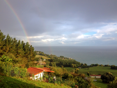 Epic rainbow falling into the sea from the hills of the Pais Basco, along the coastal Camino de Santiago, Northern Saint James Way
