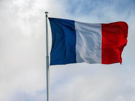 French National symbol: Deep and reach colors fabric tricolour flag of France flapping in the wind with natural blue sky background and few clouds