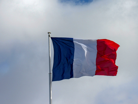 National symbol of France: Traditional texture fabric tricolor French flag waving in the wind with natural blue sky background and few clouds