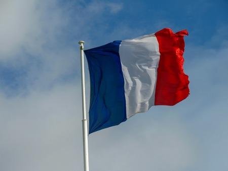 French National symbol: Bright and colorful French Tricolour fabric textile flag flapping in the wind with natural blue sky background and few clouds