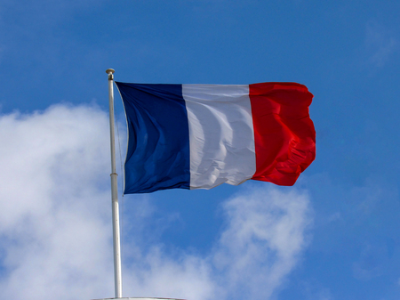Bright and colorful French Tricolour fabric textile flag flying in the high wind with natural blue sky background and few clouds and copy space
