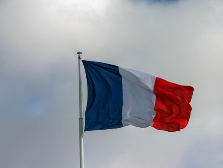 Traditional texture fabric tricolor French flag waving in the wind with natural blue sky background and few clouds and copy space Reklamní fotografie