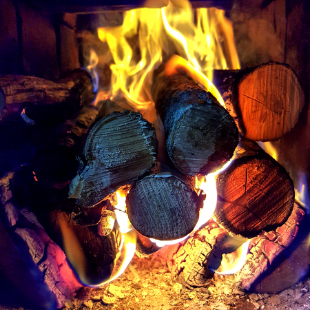 Fire flame burning coal and wood in open fireplace: charred timber and bright flames blaze on dark background