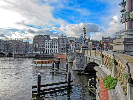 Amsterdam, Holland, Netherlands – January, 2019: Bridge on the city canal with touristic boat