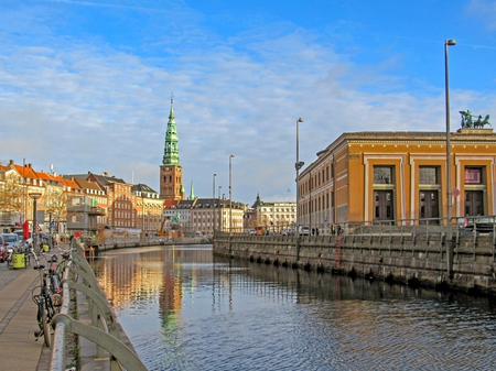 Copenhagen, Denmark - January, 2019: City canal and historical buildings of Copenhagen with Saint Nikolaj Contemporary Art Center, arts centre in Church, conspicuous landmark of Denmark