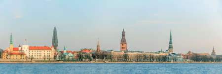 Riga old town cityscape with waterfront, old church towers and medieval castle. Panoramic view on the old Riga town across Daugava river- historical district, UNESCO heritage of Latvia, Europe Editorial