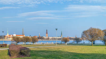 Riga old town cityscape with waterfront, old church towers and medieval castle. Panoramic view on the old Riga town across Daugava river- historical district,   Europe