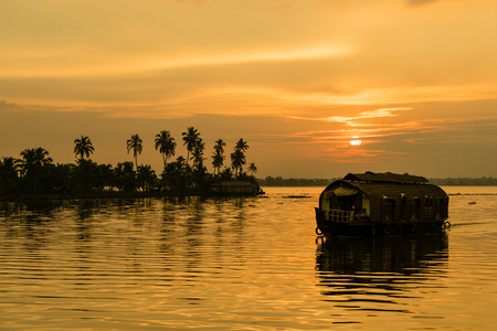 A houseboat lazily floats along the Kerala Backwaters in India.