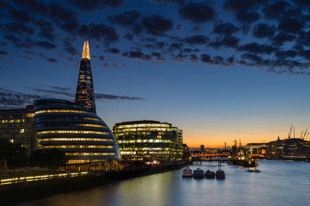 Minutes after sunset, lights illuminate Londons skyline.