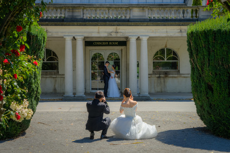 A bride and groom take pictures of another newlywed couple in a garden