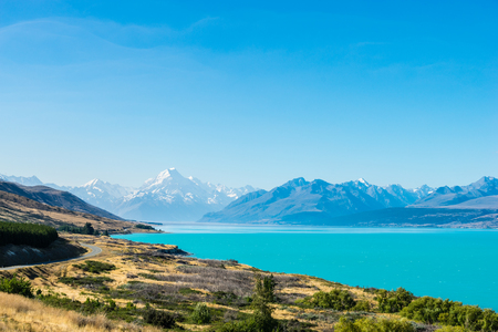 A road winds along the edge of a turquoise blue lake with mountains in the distance Stock Photo