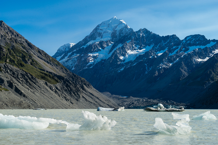 Icebergs float in a cold lake with a large snow covered mountain Stock Photo