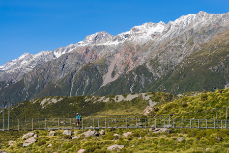 A lone hiker crosses a suspension bridge in Mount Cook National Park, New Zealand.