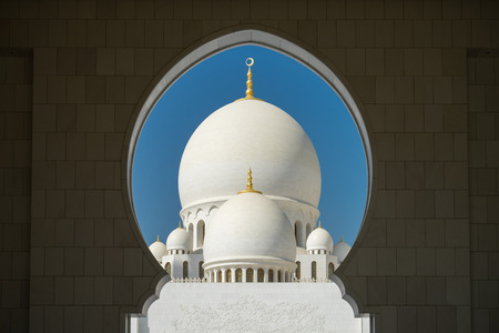 A mosque is framed by an arched passageway in Abu Dhabi, United Arab Emirates. Stock Photo