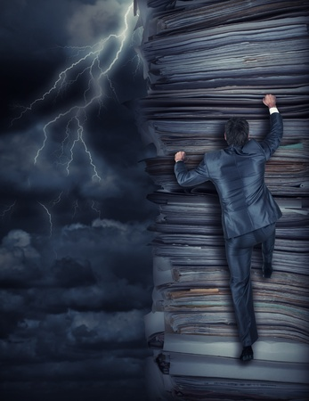 Businessmen climbing up a pile of documents at storm Stock Photo - 17922228