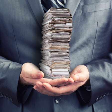 small paper: Businessman holding stack of documents