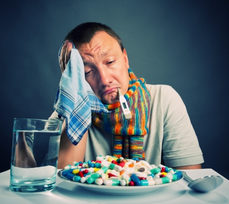 1 person: Sad ill man preparing to eat medicines