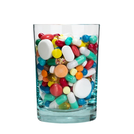 Medical cocktail - glass full of pills. Isolated photo