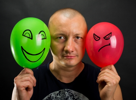 Emotionless man between happy and angry balloons Stock Photo