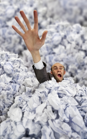 office chaos: Businessman sinking in big heap of crumpled papers and asking for help Stock Photo