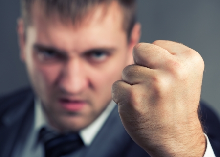 Angry businessman threaten with a fist Stock Photo
