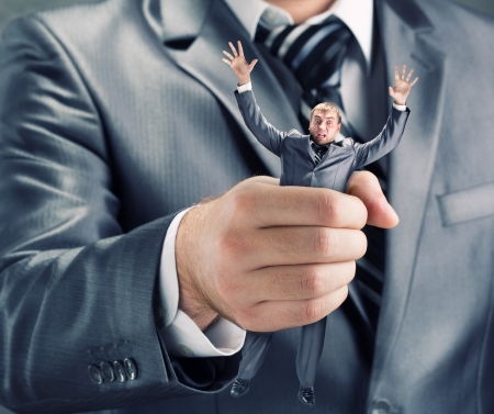 squeezing: Squeezing small businessman in hand