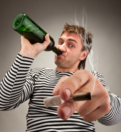 Drunk bizarre sailor with bottle and cigarette photo