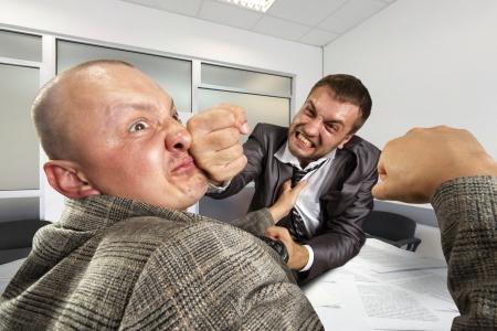 peleando: Dos hombres de negocios enojados que luchan en la oficina