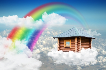 horizon over land: Small wooden house flying on cloud in sky near rainbow Stock Photo
