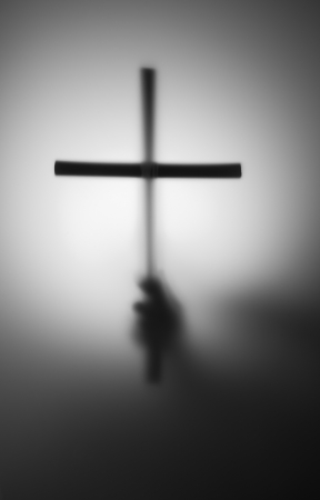 jesus hands: Blurred silhouette of hand with cross in the dark