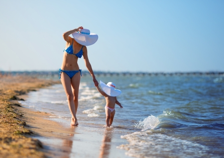 Mother and daughter walking on beach photo