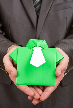 Businessman holding green origami suit in hands Stock Photo - 18033072