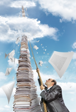 Purposeful businessman climbing up the pile of paperwork