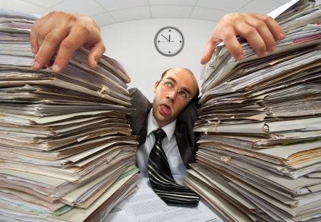 Exhausted businessman has had too much of his paperwork Stock Photo