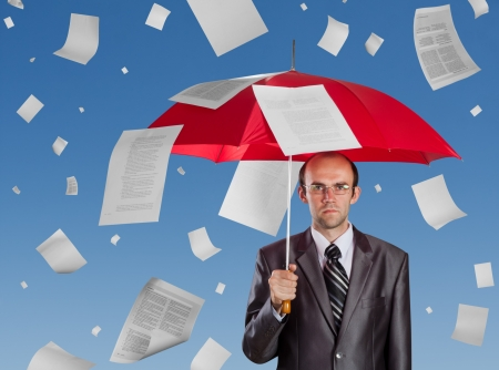 Serious businessman with red umbrella under falling documents photo