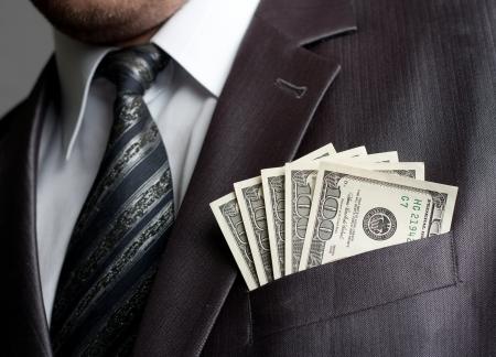 bolsa dinero: Empresario formal weared con el dinero ganado en el bolsillo de traje