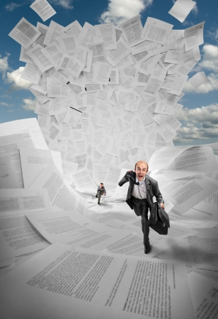 Scared businessmen running away from huge wave of documents photo
