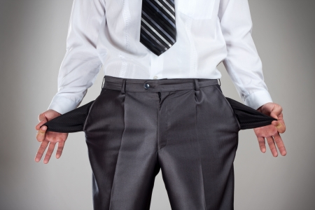 moneyless: Businessman pulling empty pockets out of pants