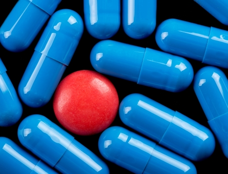 Special red pill between blue capsules Stock Photo - 18055274